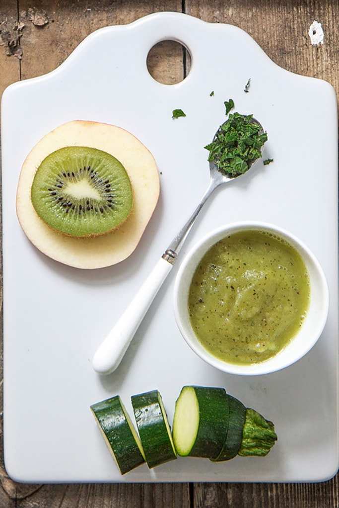 White board with a slice of apple and kiwi stacked on top of each other, a slice zucchini at the bottom and a silver and white spoon with chopped mint inside. On the right hand side is a small white bowl filled with the baby food puree.