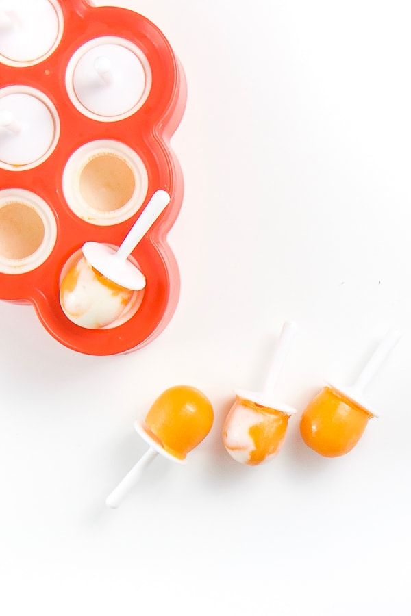 white background with a zoku popsicle mold in the corner and three hidden veggie healthy toddler snack popsicles coming out of it.