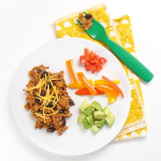 round white plate with a taco meal for baby - finger foods of turkey taco meat with beans and a sprinkle of cheese, on the side - chunks of avocado, strips of peppers and chunks tomatoes.
