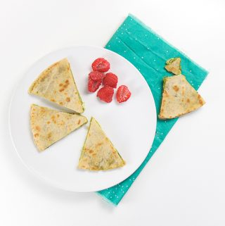 white round plate with wedges of kale pesto quesadilla and a side of chopped raspberries. The plate is sitting on a teal napkin and there is a torn wedge of quesadilla on it.