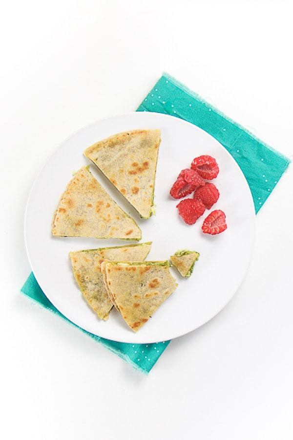 round white plate with wedges of kale pesto chicken quesadilla with a side of chopped raspberries. plate is sitting on a teal napkin on a white surface.