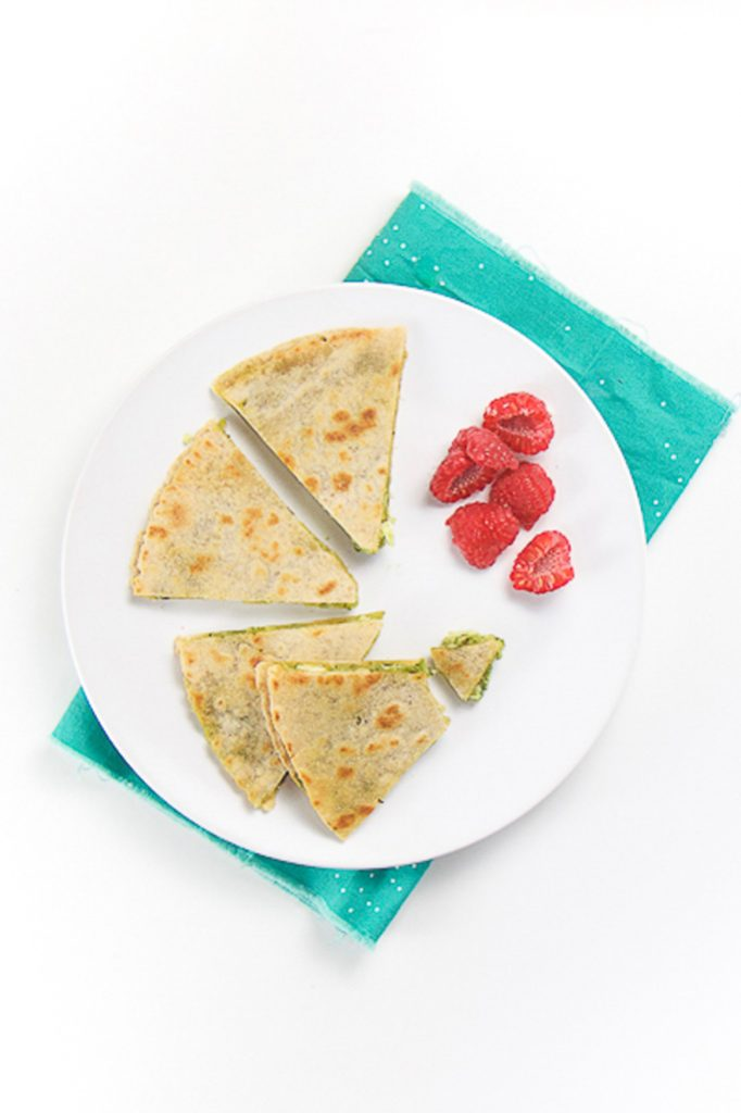 round white plate sitting on top of a teal napkin. On the plate is a baby and toddler meal idea - 4 wedges of baby-led weaning kale and chicken quesadilla, one wedge has a bite taken out of it. Side of chopped raspberries make for great finger foods for baby