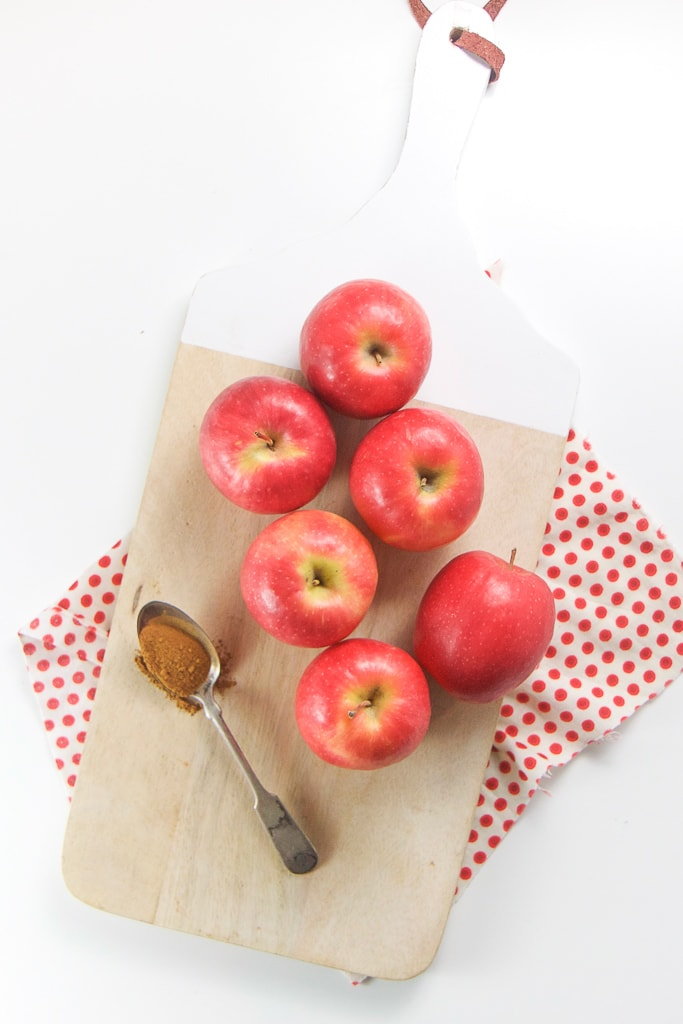 wood cutting board with 6 red apples on top and a spoonful of cinnamon sitting on a white board.