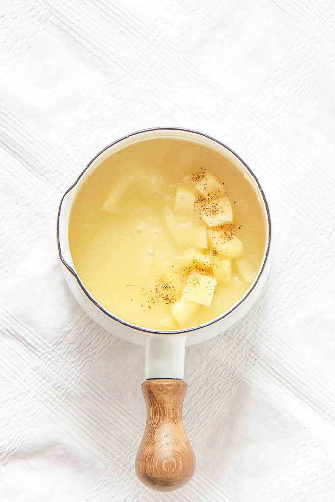 Image is of a small white saucepan on top of a white tablecloth filled with apple baby recipe and sprinkled with chunks of apples and cloves - baby food for 4 months and up