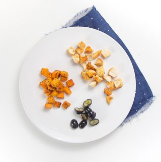 white round plate on top of a dark blue napkin. On the plate is finger foods for baby or toddler - chopped seasoned chicken, blueberries and sweet potatoes