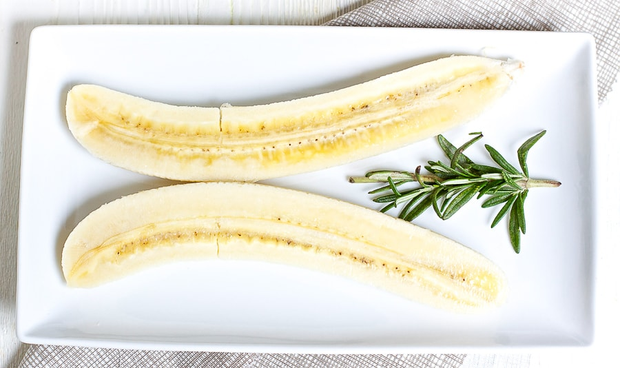 white long rectangle plate with a banana sliced up lengthwise, a sprig of rosemary is in-between banana slices.