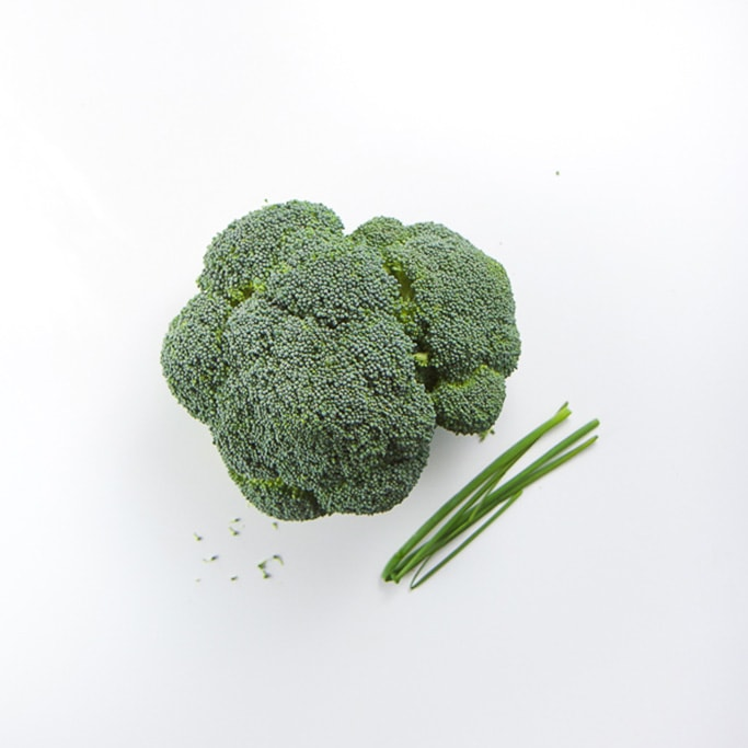 a head of broccoli and a few stalks of chives sitting on a white background
