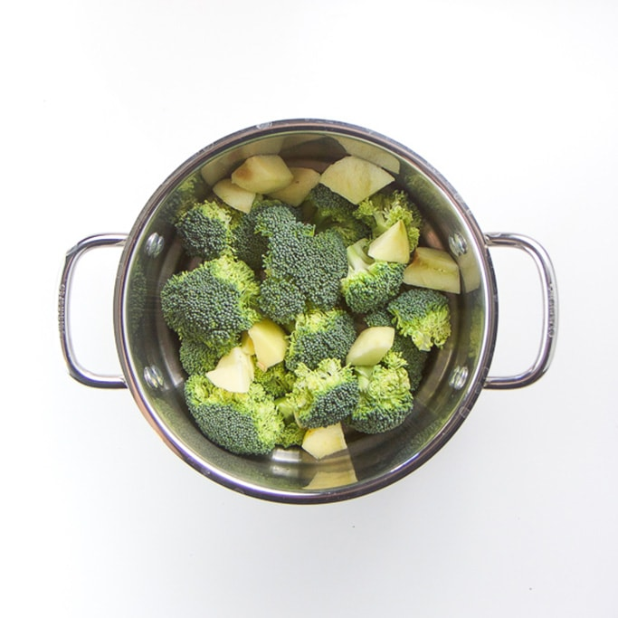 silver steamer basket filled with broccoli and a potato.