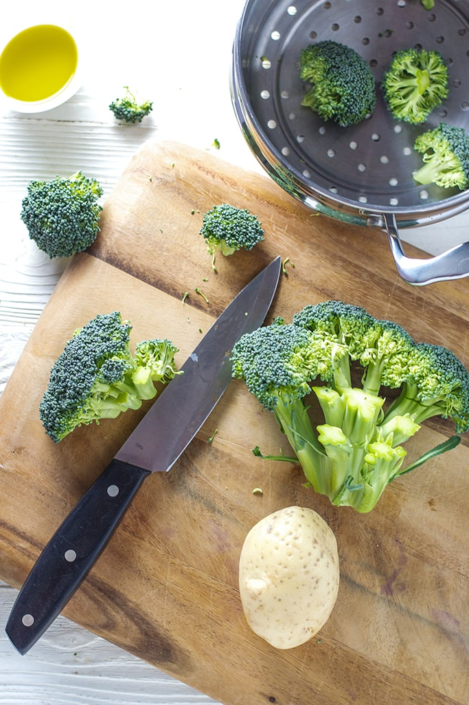 a wooden cutting board that has broccoli florets and potato on it getting ready to be cut. A silver steamer basket sits next to the board with a few broccoli pieces in it.