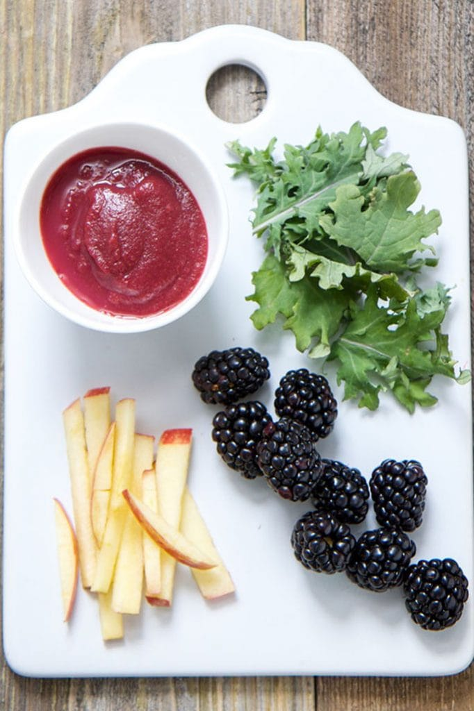 A white cutting board sitting on a wood board. On the white board is apple slices, blackberries and baby kale with a small white bowl filled with a baby food puree recipe.