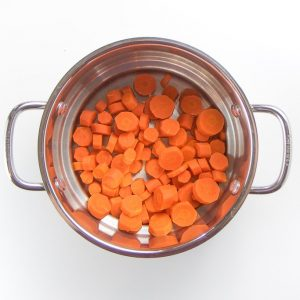 chopped carrots in a steamer basket.