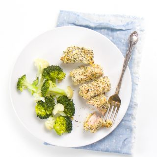 round white plate on top of a blue napkin. On the plate is 4 salmon bites coated in breadcrumbs and herbs. On the side is steamed broccoli and cauliflower.