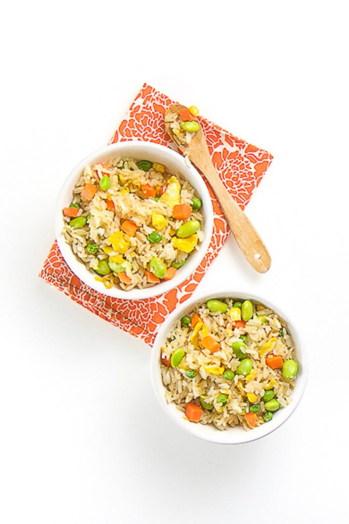 2 white bowls filled with brown rice, vegetables and scrambled egg chunks. Bowls are sitting on a orange flower napkin. There is a wooden spoon on top of one of the bowls with the rice in in.