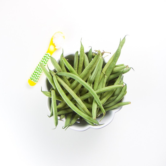 small white bowl with scalloped edges sitting on a white background filled with fresh green beans. Yellow and green spoon sitting next to bowl filled with coconut oil