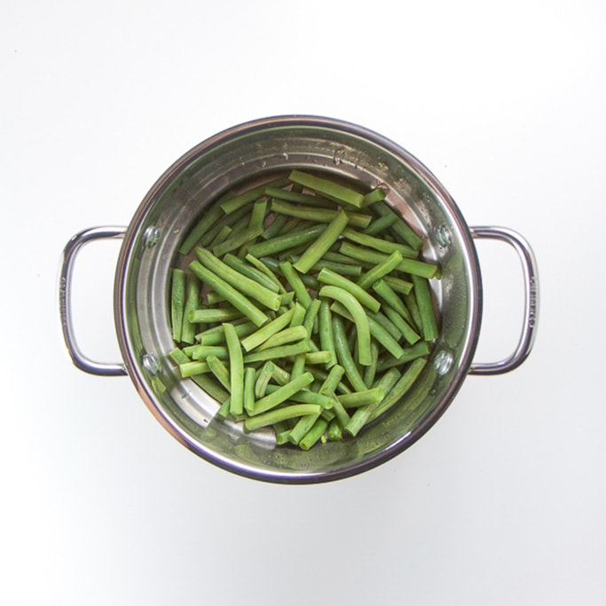 silver steamer sitting on a white background filled with chunks of steamed green beans
