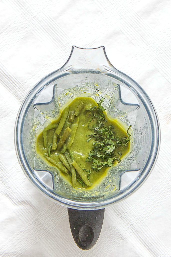 blender sitting on top of a white tablecloth, inside is a homemade green bean puree with chunks of green beans and basil sprinkled on top.