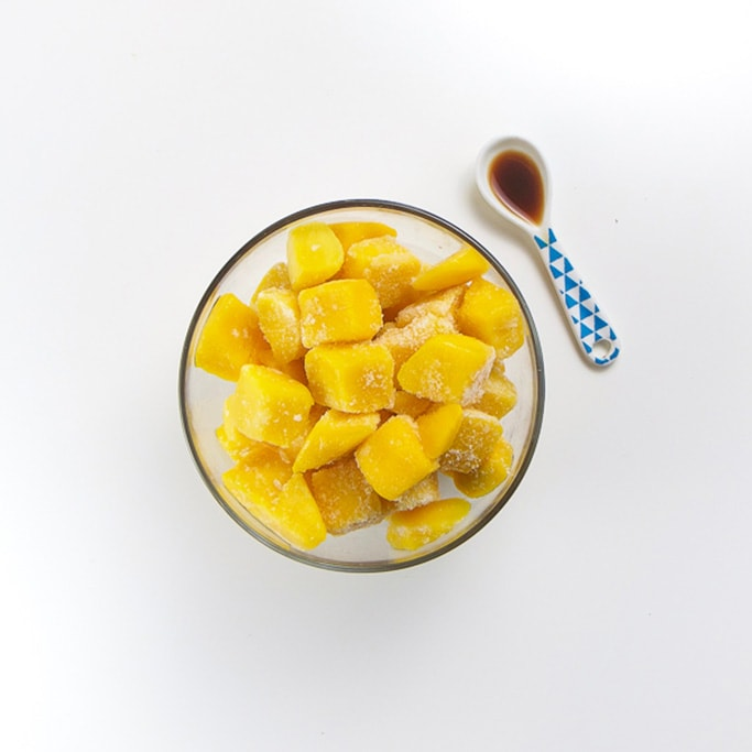 clear glass bowl filled with frozen mango chunks with a small white and blue spoon sitting next to it filled with vanilla bean extract