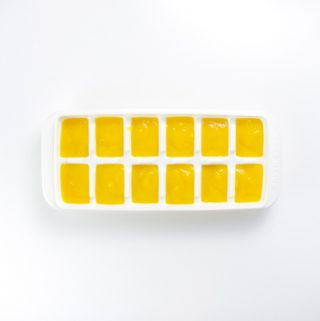 white freezer tray sitting on a white background filled with a creamy organic mango baby food recipe