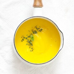 small white saucepan sitting on top of a white tablecloth filled with a creamy mango baby food puree with a sprinkle of mint on top of the puree.