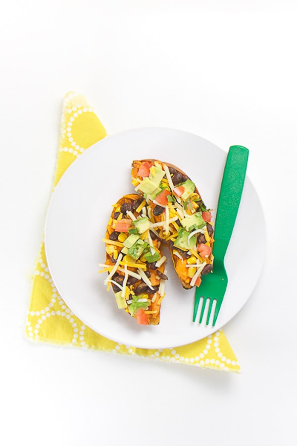 white round plate on top of a yellow napkin. on plate is a cut in half sweet potato topped with avocado, beans, tomato chunks, cheese and cilantro.