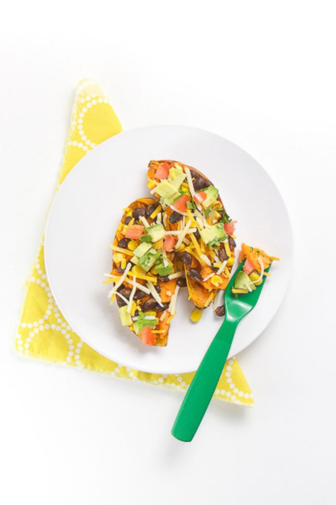 white round plate sitting on a yellow napkin with 2 halves of a sweet potato on top loaded with healthy toppings, great for toddler lunch idea