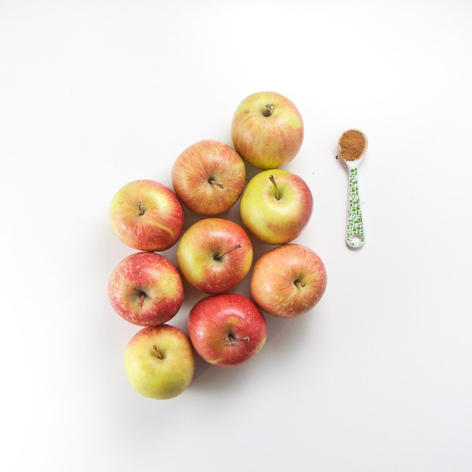 9 apples sitting on a white background in a triangle with a small white and green spoon filled with ground cloves sitting next to the apples.