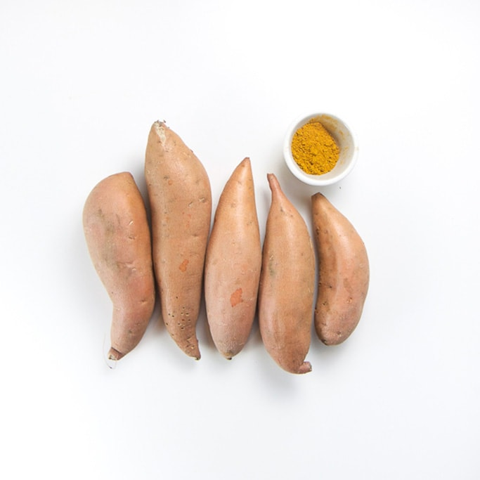 5 small sweet potatoes lined up in a row with a small bowl filled with a mild curry spice inside.