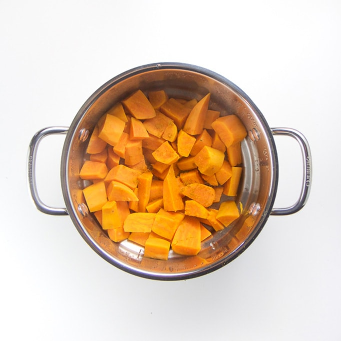 silver steamer basket filled sitting on a white background filled with steamed sweet potato chunks