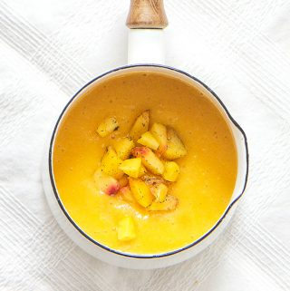 small white saucepan on top of a white tablecloth filled with peach and vanilla baby food puree with chunks of peaches and vanilla bean sprinkled on top - baby food for 4 months and up
