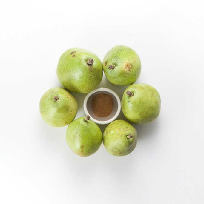 6 green pears on a white background in a circle. Inside the circle is a small bowl with ground clove inside.