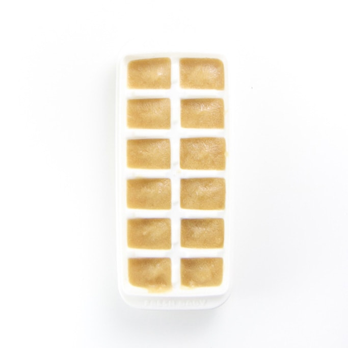 a white freezer tray on a white background filled with a pear baby food puree - freezer-friendly