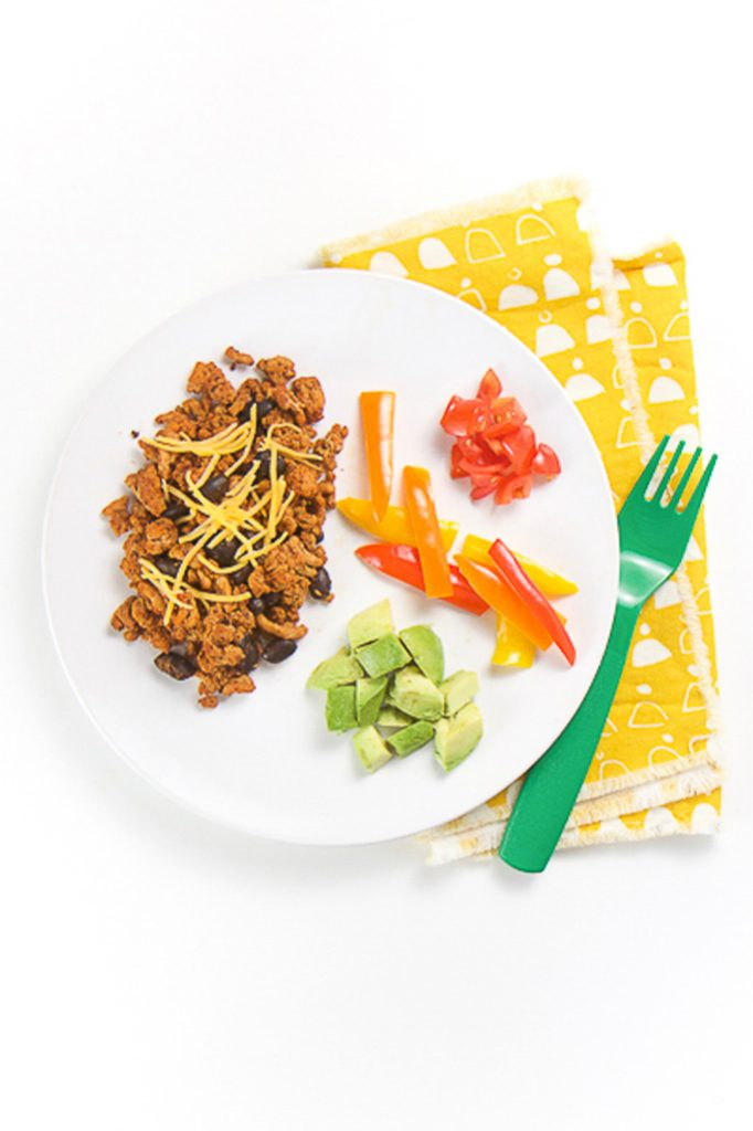 round white plate sitting on a bright yellow napkin. On the plate is a pile of ground turkey with beans sprinkled with cheese and a side of chopped tomatoes, sliced peppers and avocado chunks - great for baby-led weaning