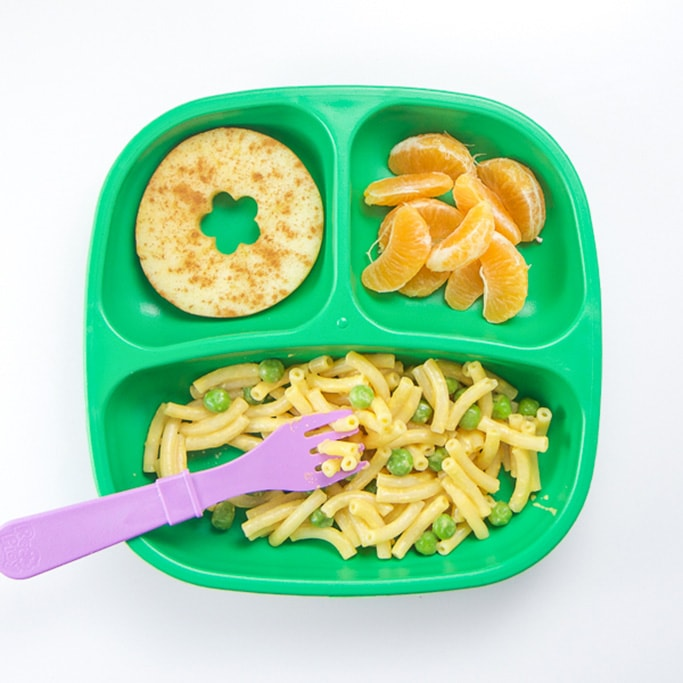 A 3-section plate filled with mac and cheese with peas, cinnamon apple slice and orange sections.