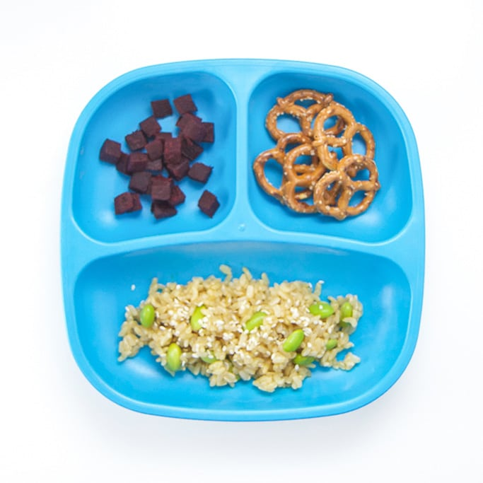 A 3-section plate on a white surface filled with mango rice, pretzels and chopped beets