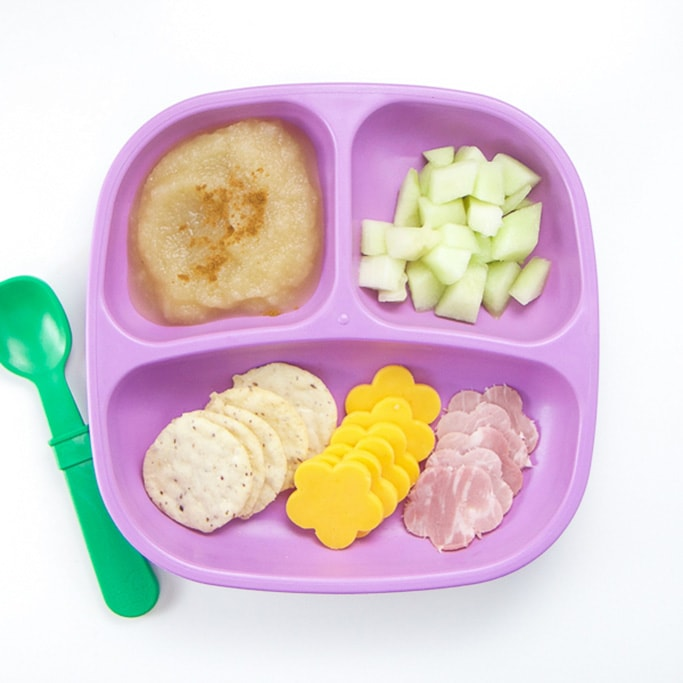 A 3-section plate filled with slices of cheese and crackers, pear sauce and shipped veggies