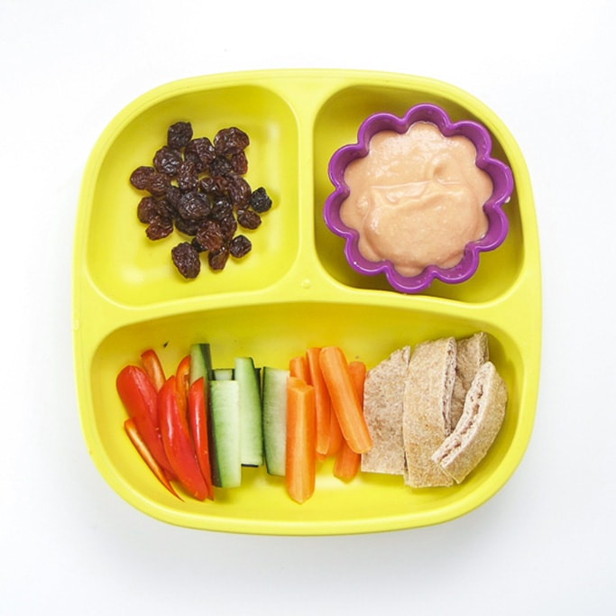 A 3-section plate on a white surface filled with chopped veggies, pita, hummus and raisins - a healthy lunch idea for toddler
