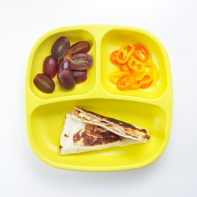 A 3-section plate on a white surface filled with quesadilla, cut grapes, sliced peppers.