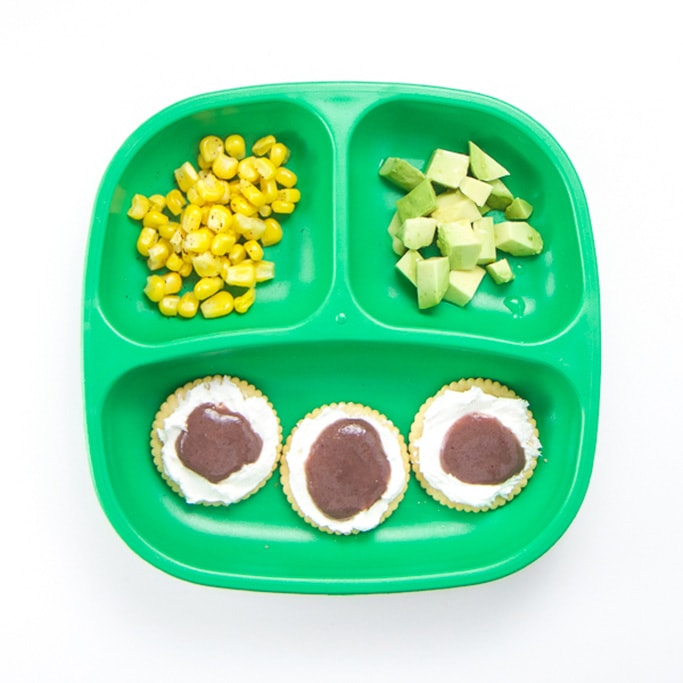 A 3-section plate filled with cream cheese crackers, chopped avocado and spiced corn - a healthy toddler lunch idea