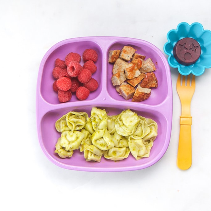 3-section plate on a white surface filled with toddlers dinner - cheese tortellini with pesto sauce, meatballs and raspberries with a gummy for dessert.