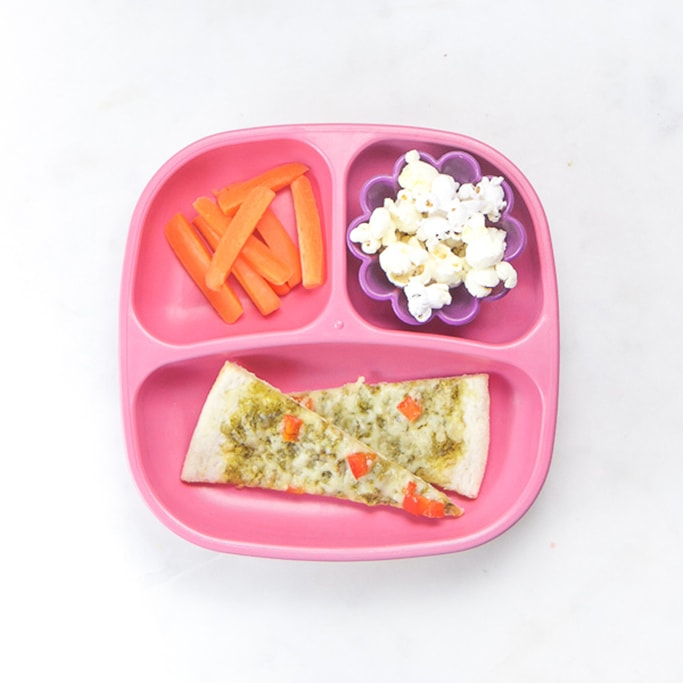 3-section plate on a white surface filled with healthy toddler meals - 2 slices of pizza, carrot sticks and popcorn.