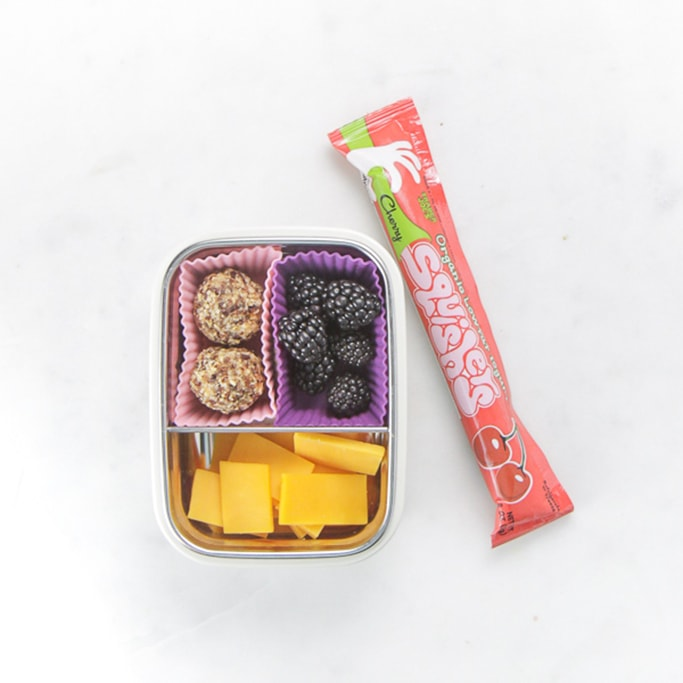 white bento filled with cheese, blackberries and fruit balls with a yogurt squeeze beside it.