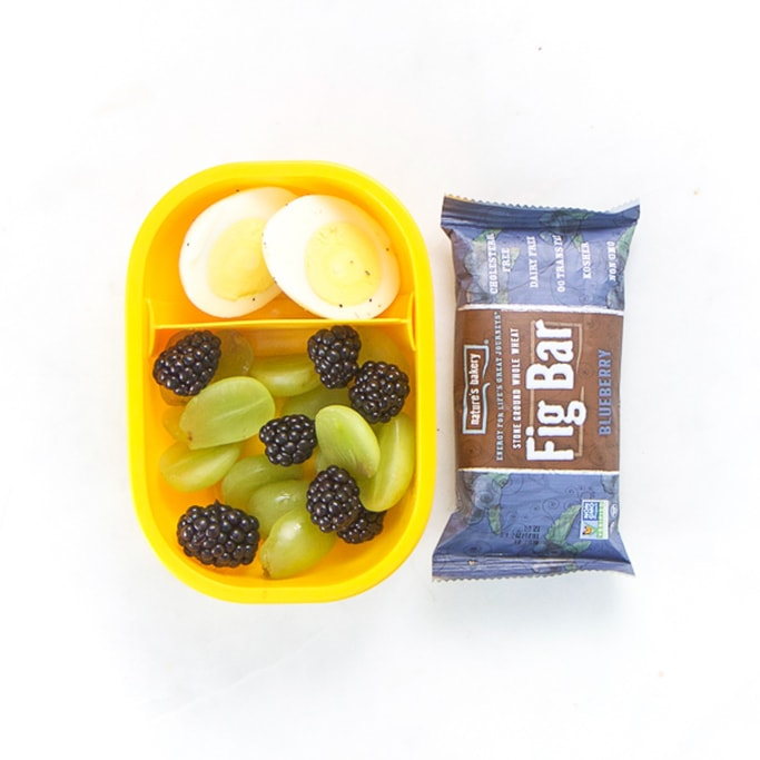 yellow bento box on white surface filled with cut grapes and blackberries and a hardboiled egg. Also next to the bento is a fig bar.