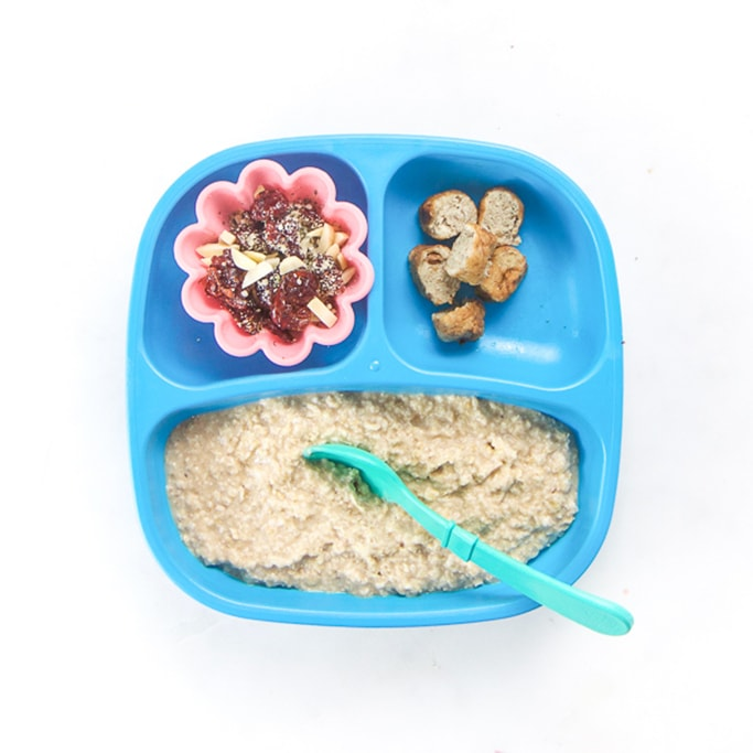 3-section plate on a white surface filled with toddlers breakfast meal - DIY oatmeal with cup of dried fruit and nuts, sliced chicken apple sausage.