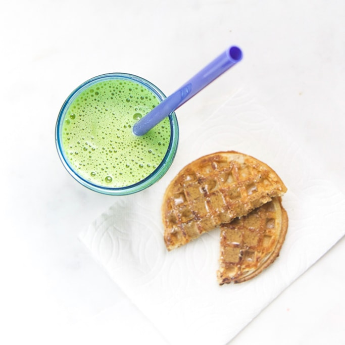 green smoothie in blue toddler cup sitting on white surface with a waffle cut in half on a white napkin.
