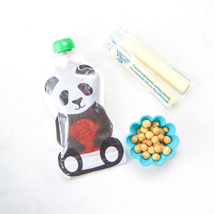 toddler snacks on a white surface - pouch, cereal and string cheese.
