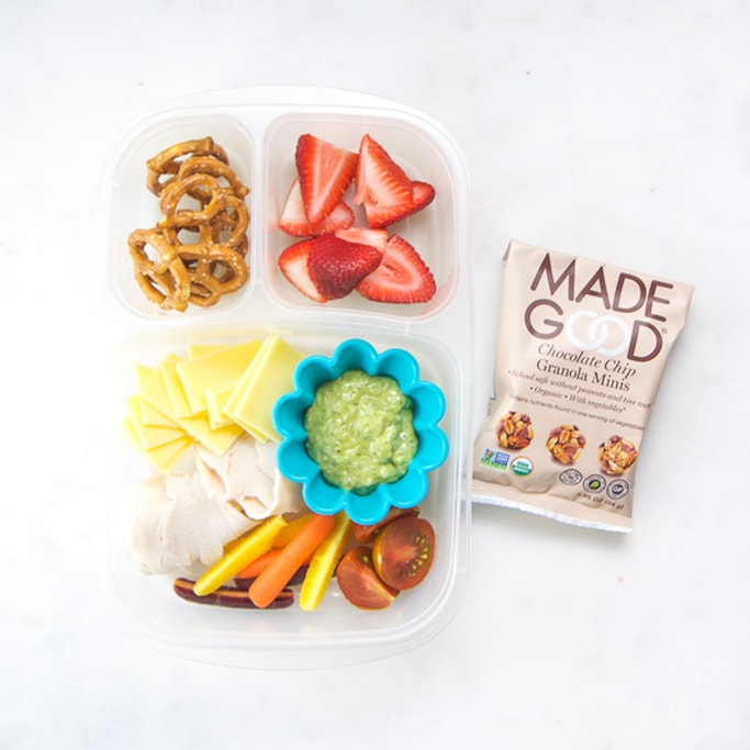 Clear bento no white surface filled with turkey, cheese, carrots and tomatoes with an avocado dipping sauce, chopped strawberries and pretzels with a packed snack.