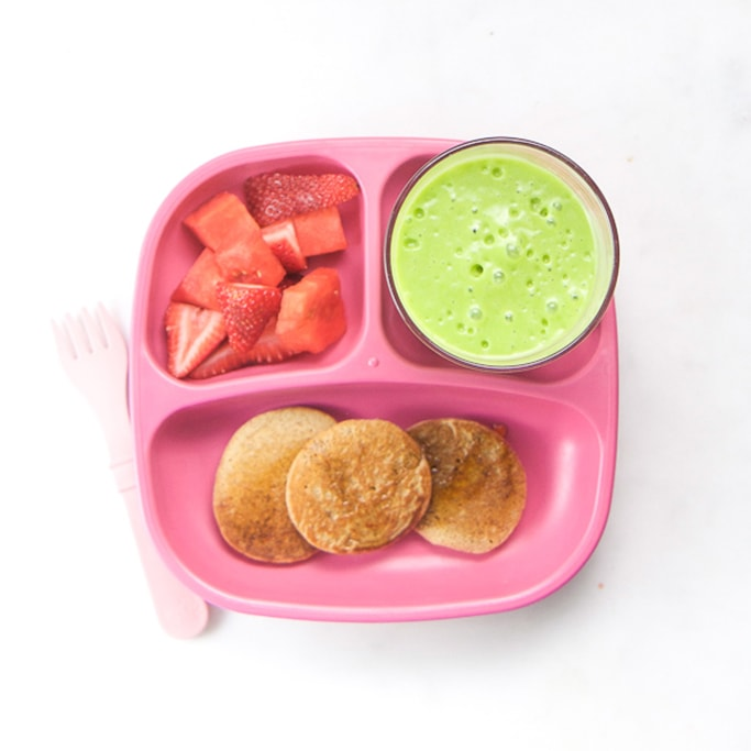 3-section plate on a white surface filled with toddlers breakfast meal - blender pancakes, green smoothie and chopped strawberries.