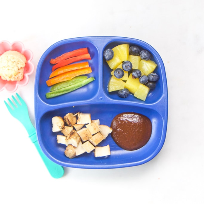 3-section plate on a white surface filled with healthy toddler meals - chopped chicken with bbq sauce, pineapple and blueberries, sliced peppers and a coconut cookie.
