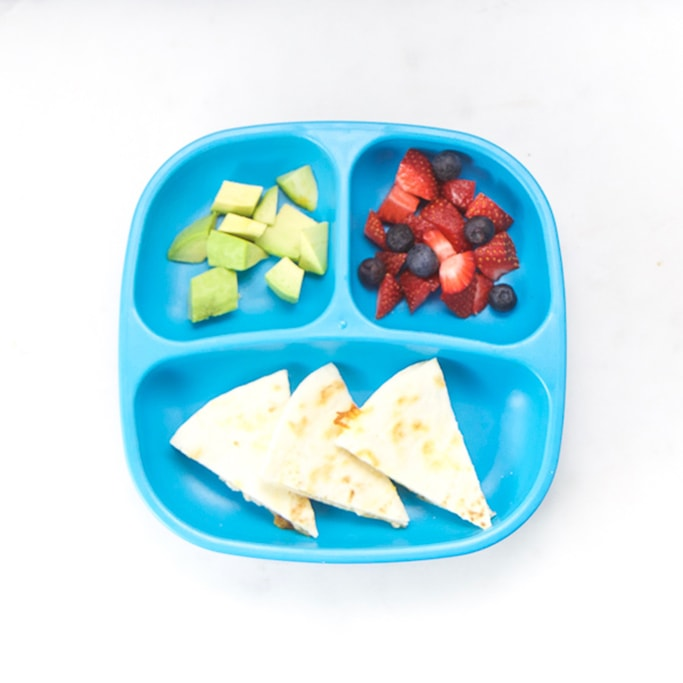 3-section plate on a white surface filled with toddlers lunch meal - cut wedges of bean quesadilla, fruit and avocado.