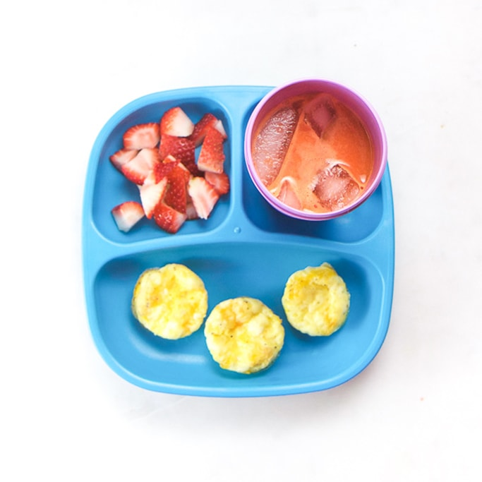 3-section plate on a white surface filled with toddlers breakfast meal - eggs, strawberries and pressed juice.
